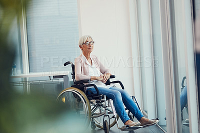 Buy stock photo Full length shot of a senior woman looking thoughtful while sitting in her wheelchair at a retirement home