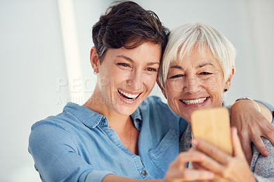 Buy stock photo Cropped shot of an affectionate young woman taking a selfie with her aged mother at home