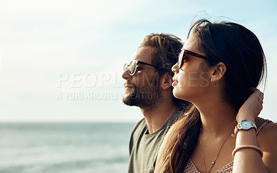 Buy stock photo Cropped shot of an affectionate young couple looking out at the ocean together during a road trip
