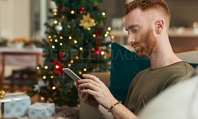 Buy stock photo Shot of a young man using a smartphone on the sofa at home during Christmas