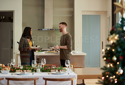 Buy stock photo Shot of a young man and woman setting a table for a Christmas party at home