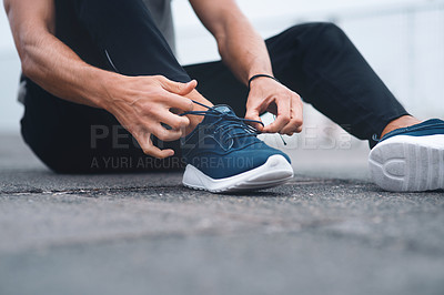 Buy stock photo Closeup shot of an unrecognisable man tying his laces while exercising outdoors