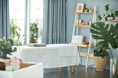 Buy stock photo Shot of a tranquil massage room with plant life and a massage bed during the day