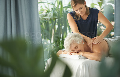 Buy stock photo Cropped shot of a relaxed senior woman lying down and enjoying a massage at the spa during the day