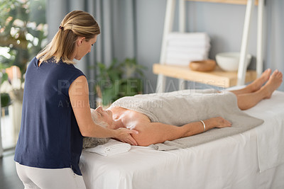 Buy stock photo Full length shot of a relaxed senior woman lying down and enjoying a massage at the spa during the day