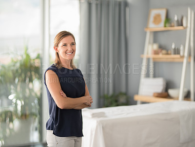 Buy stock photo Cropped portrait of an attractive mature masseuse smiling and standing with her arms crossed in the spa during the day