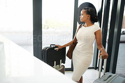 Buy stock photo Shot of a beautiful young woman standing with her luggage and checking in at a hotel