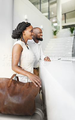 Buy stock photo Shot of a happy young couple checking in at the reception of a hotel