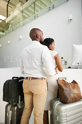 Buy stock photo Rearview shot of an affectionate young couple standing with their luggage at the reception of a hotel