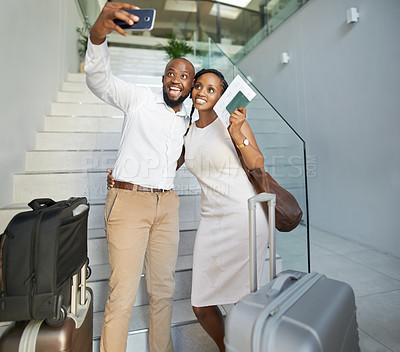 Buy stock photo Shot of an affectionate young couple taking selfies with a cellphone while checking in at the reception of a hotel