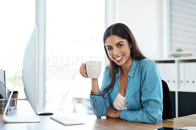 Buy stock photo Portrait of a young businesswoman drinking coffee while working on a computer in an office