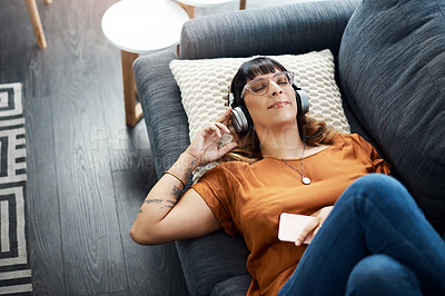 Buy stock photo Shot of a young woman wearing headphones while relaxing at home