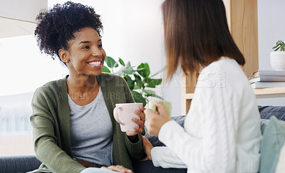 Buy stock photo Cropped shot of two attractive young women sitting together and drinking coffee while at home during the day