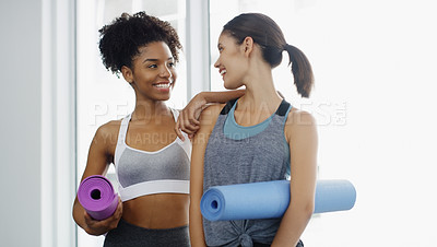Buy stock photo Cropped shot of two attractive young women standing and holding yoga mats and posing before working out indoors