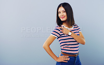 Buy stock photo Studio shot of an attractive young woman pointing at copy space against a grey background