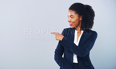 Buy stock photo Studio shot of an attractive young businesswoman pointing at copy space against a grey background