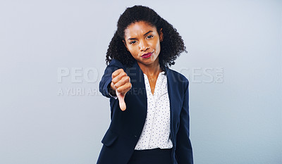 Buy stock photo Studio shot of an attractive young businesswoman giving thumbs down against a grey background