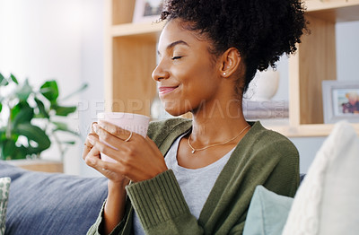 Buy stock photo Cropped shot of an attractive young woman holding a coffee mug while sitting on the sofa in her living room