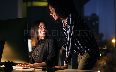 Buy stock photo Cropped shot of two attractive young businesswoman working together while in the office late at night