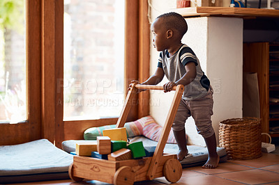 Buy stock photo Shot of a toddler pushing a toy cart with block inside of it inside of his bedroom at home during the day