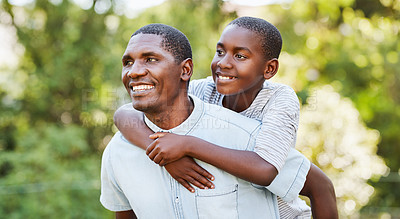 Buy stock photo Cropped shot of a cheerful middle aged man carrying his son on his back while walking around in a park outside during the day