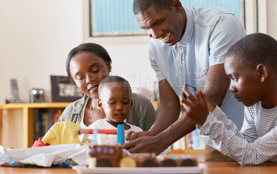 Buy stock photo Cropped shot of a cheerful young family celebrating their little toddler son's birthday while he opens a present at home during the day