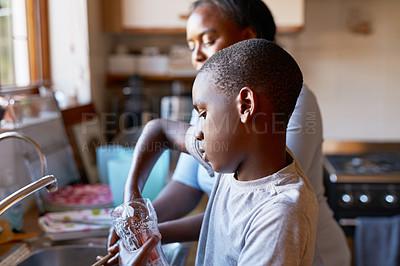 Buy stock photo Cropped shot of a cheerful young boy and his mother washing hands together in the kitchen at home