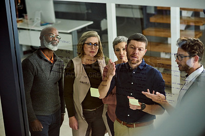 Buy stock photo Cropped shot of a group of designers brainstorming on a glass board