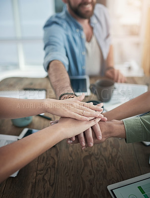 Buy stock photo Cropped shot of a group of businesspeople joining hands during a meeting in a modern office