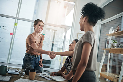 Buy stock photo Shot of young businesswomen shaking hands during a meeting in a modern office