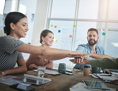 Buy stock photo .Shot of a group of young businesspeople joining hands during a meeting in a modern office