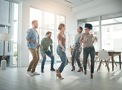 Buy stock photo Shot of a group of young businesspeople dancing in a modern office