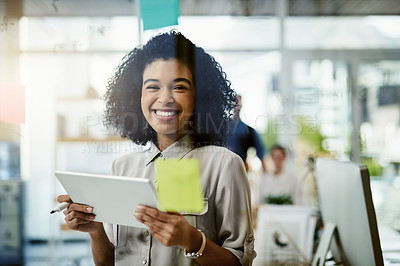 Buy stock photo Portrait of a young businesswoman using a digital tablet while brainstorming with notes on a glass wall in an office