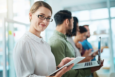 Buy stock photo Portrait of a young businesswoman using a digital tablet while standing in line with her colleagues in an office