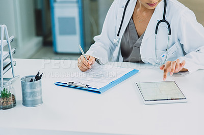 Buy stock photo Cropped shot of an unrecognizable doctor multitasking by using a tablet and writing on a clipboard while in her office