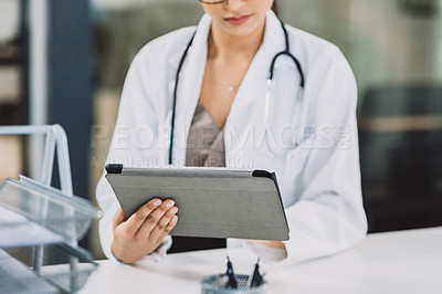 Buy stock photo Cropped shot of an unrecognizable doctor working on a tablet while in her office during the day
