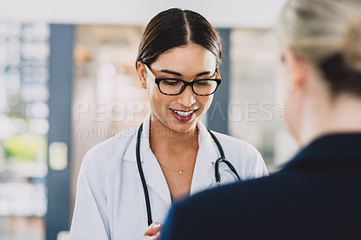 Buy stock photo Cropped shot of an attractive young doctor smiling and standing with a colleague while indoors during the day