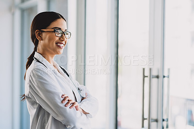 Buy stock photo Cropped shot of an attractive young doctor standing with her arms crossed and smiling while in her office