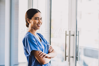Buy stock photo Cropped shot of an attractive young nurse standing with her arms folded and smiling while in her office