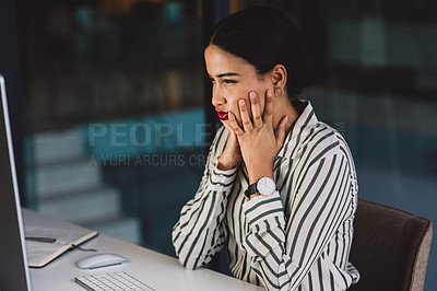 Buy stock photo Shot of a young businesswoman looking confused while working on a computer in an office at night