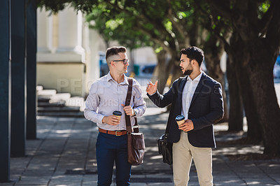 Buy stock photo Shot of two young businessmen having coffee and chatting while walking though the city