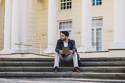 Buy stock photo Shot of a young businessman sitting on steps and using a digital tablet in the city