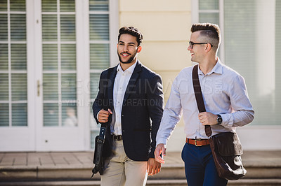 Buy stock photo Shot of two young businessmen chatting while walking though the city