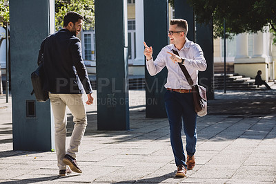 Buy stock photo Shot of two young businessmen greeting each other while walking through the city