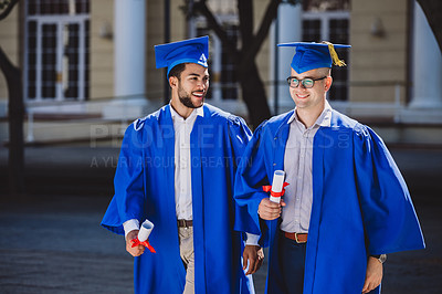 Buy stock photo Shot of two young men walking and chatting on graduation day