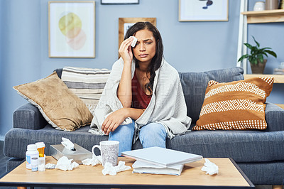 Buy stock photo Shot of an attractive young woman suffering from a cold while spending the day at home