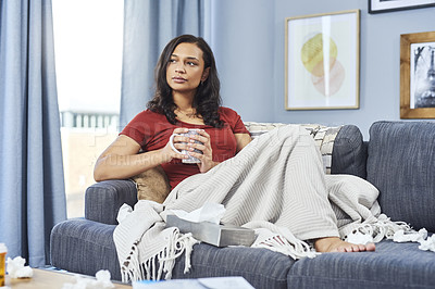 Buy stock photo Shot of an attractive young woman feeling sick and having a cup of hot tea at home