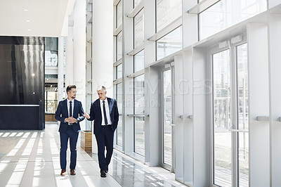 Buy stock photo Full length shot of two handsome businessmen having a discussion while walking through the office during the day