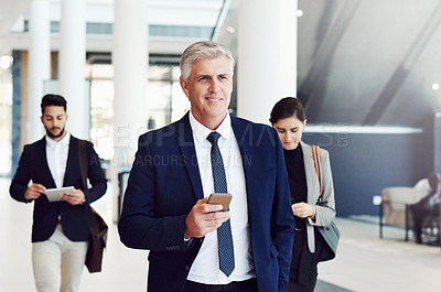 Buy stock photo Cropped shot of a group of businesspeople using technology while walking through the office during the day