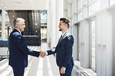 Buy stock photo Cropped shot of two handsome businessmen shaking hands in agreement while standing in the office during the day